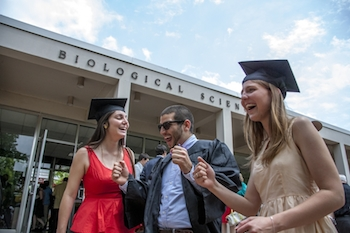 A male in his graduation gown and two females in their graduation camps rejoice outside of the Biosciences building before their reception.